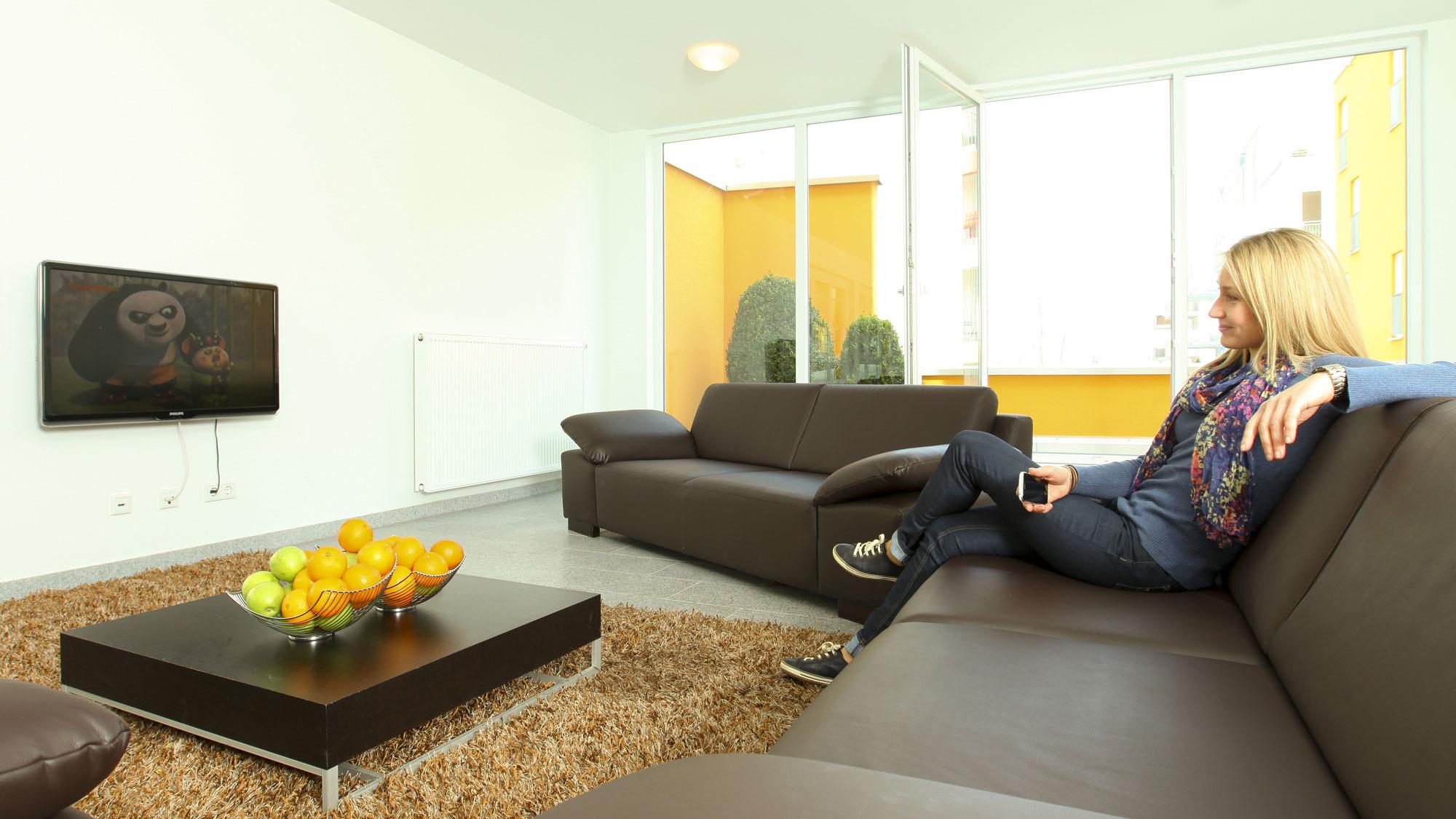 Frau sitzt auf der Couch im Wohnzimmer mit angrenzendem Balkon eines Studentenapartments in der Wohnanlage studiosus 1 ins Regensburg
