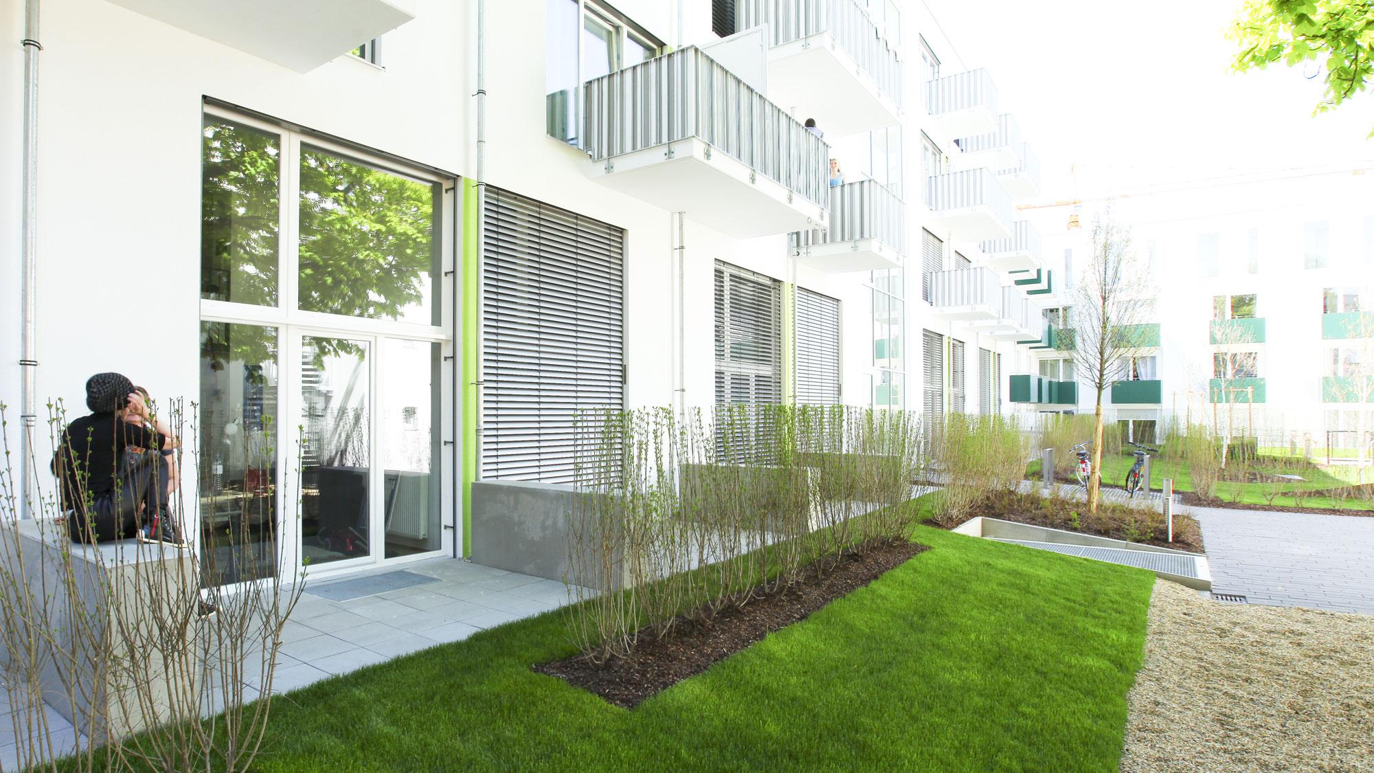 Hofseite des Neubauprojekts studiosus 2 in Regensburg mit Blick in den Garten sowie die Terassen und Balkone der Studentenapartements